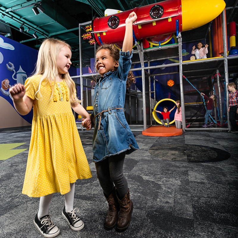 Two girls jumping in Inagination destination