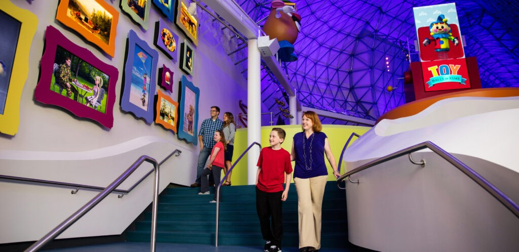 Two families walking down the stairs at The Strong Museum while chatting about the different images of Play that are hung on the wall.