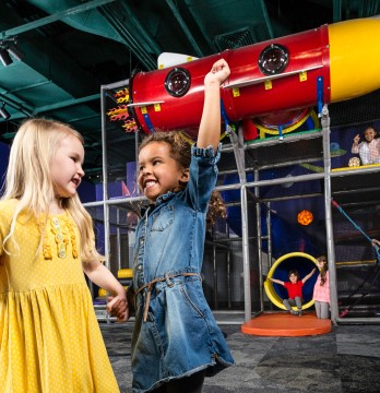 An two little girls holding hands and gesturing excitedly while they play at The Strong museum.