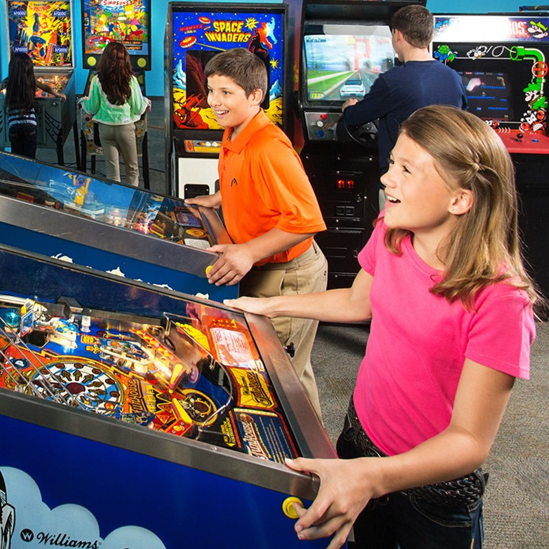 Kids playing pinball closeup