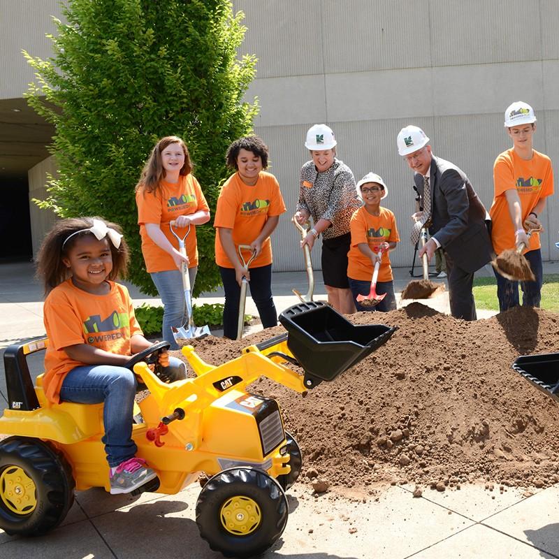 Groundbreaking ceremony shoveling dirt with kids